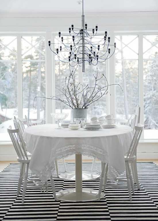 белый обеденный стол и красивая люстра