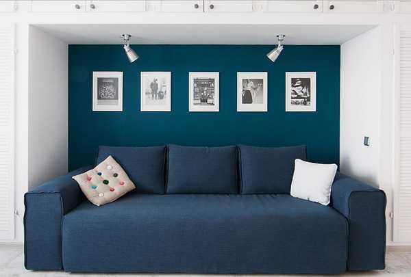 синий диван, фоторамки на синей стене