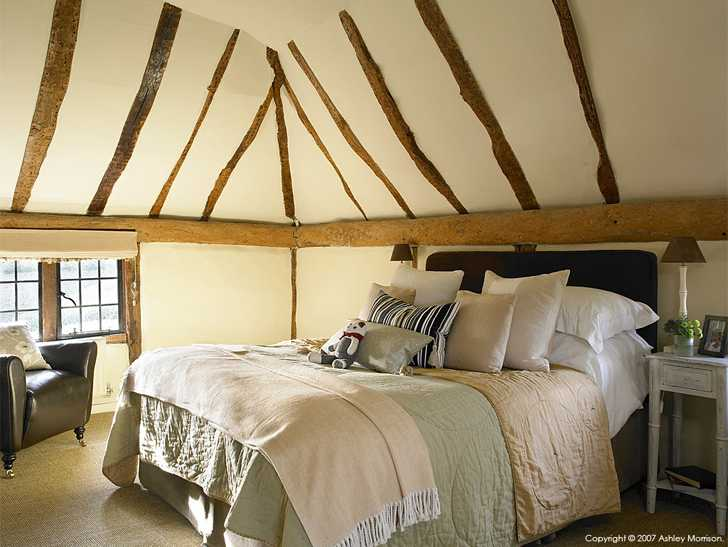 Bedroom in Beth and Jason Cooper's 16th-century old school house near Guildford in Surrey.