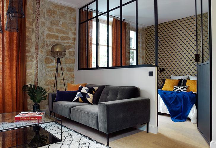 Небольшая квартира с каменной стеной и стеклянной перегородкой в Париже