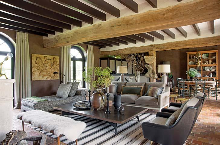 Деревянные балки на потолке и каменный пол в интерьере французского дома