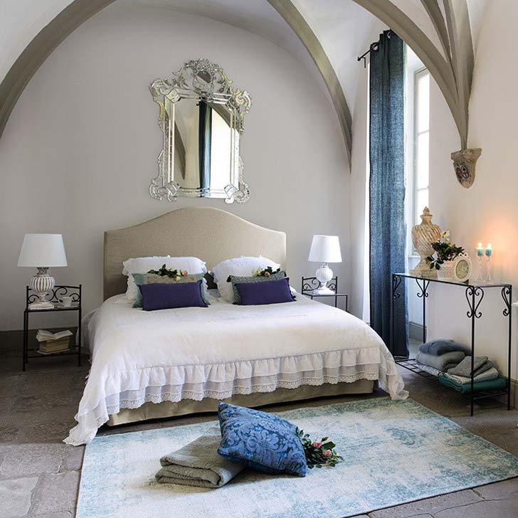 Спальная комната в пастельных цветах и с каменным полом