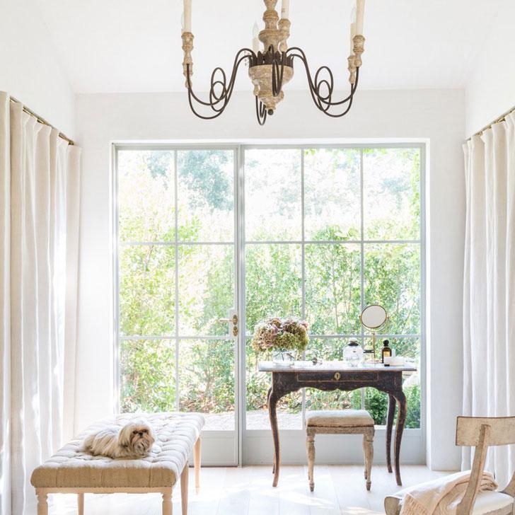 Классическая люстра, кушетка и столик в небольшой комнате