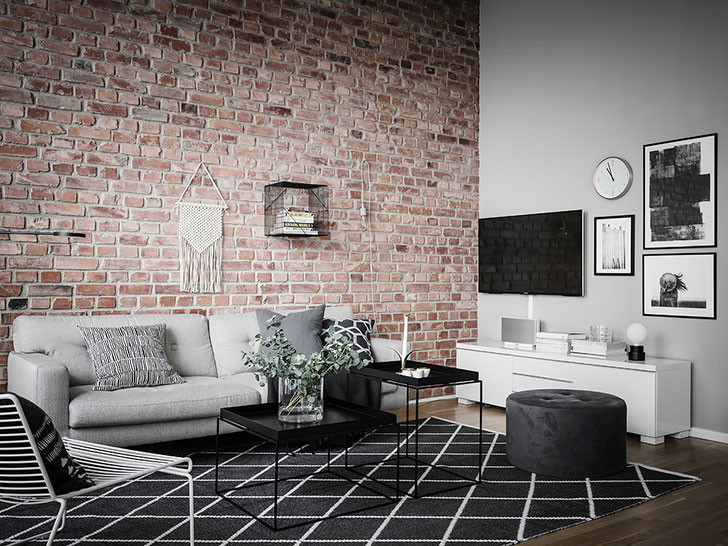 Кирпичная стена в гостиной и черная спальня: квартира в Швеции (59 кв. м)