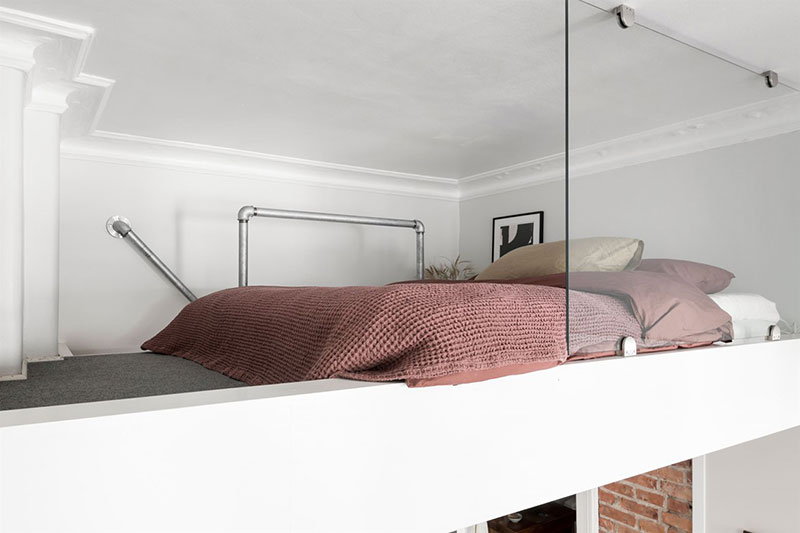 Кирпич, грубое дерево и спальня на антресоли: интересная небольшая квартира в Швеции (35 кв. м)