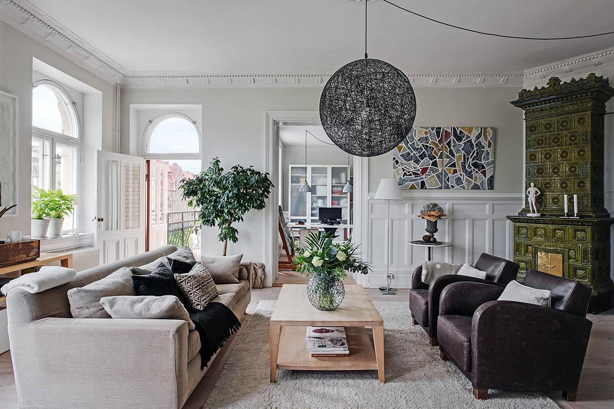 Просторная кухня с островом и библиотека в столовой: большая квартира в Швеции